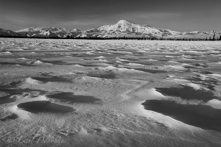 Black and white photo of Mount Sanford, one of the highest peaks in the Wrangell Mountains, at dawn, from a small frozen kettle pond. Winter snow creates patterns on the frozen lake. Mt. Sanford, Wrangell - St. Elias National Park and Preserve, Alaska.