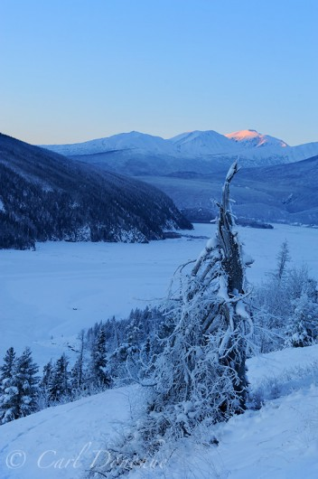 The Chitina River, frozen in winter, and it's confluence with the Copper River, as the early sunrise begins over the Chugach Mountains. Alpenglow catches the peaks of the mountains, as the frozen river valley awaits the morning glow. Chitina River, Copper River and the Chugach Mountains, Wrangell - St. Elias National Park and Preserve, Alaska.
