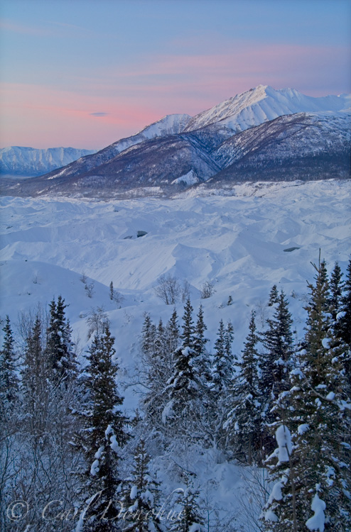 Dawn rises over Fireweed Mountain, wintertime, in the Wrangell Mountains. Looking across the Kennicott Glacier moraine, Wrangell St. Elias National Park and Preserve, Alaska.