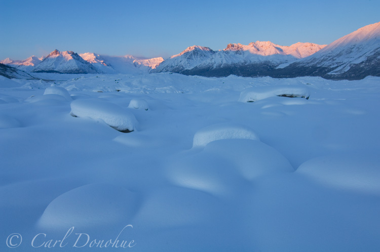 Snow-covered boulders of the Kennicott Glacier moraine. In the distance lie Bonanza Ridge, Regal Mountain and Donoho Peak, of the Wrangell Mountains. Wintertime at Kennicott, Wrangell - St. Elias National Park and Preserve, Alaska.