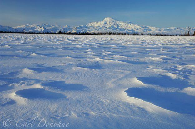 Photo of Mount Sanford, one of the highest peaks in the Wrangell Mountains, at dawn, from a small frozen kettle pond. Winter snow creates patterns on the frozen lake. Mt. Sanford, Wrangell - St. Elias National Park and Preserve, Alaska.