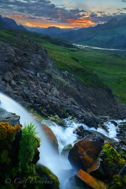 A waterfall glows in the light of a colorful sunset. Near Chitistone Pass, looking toward Skolai Pass, Wrangell - St. Elias National Park and Preserve, Alaska.