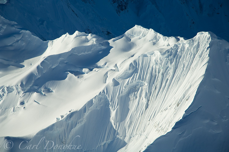 A fresh snowfall covers this fluted, jagged aréte high in the St. Elias Mountain Range. Aerial Photo.