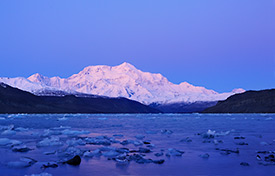 Mount Saint Elias glows in the soft after dusk alpenglow of the winter sky. Icy Bay in the foreground is littered with scattered icebergs, remnants from the many glaciers in the area. Mount Saint Elias and Icy Bay, Wrangell - St. Elias National Park and Preserve, Alaska.